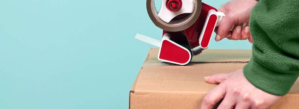 man taping box closed