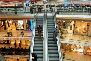 Shopping center patrons on escalator