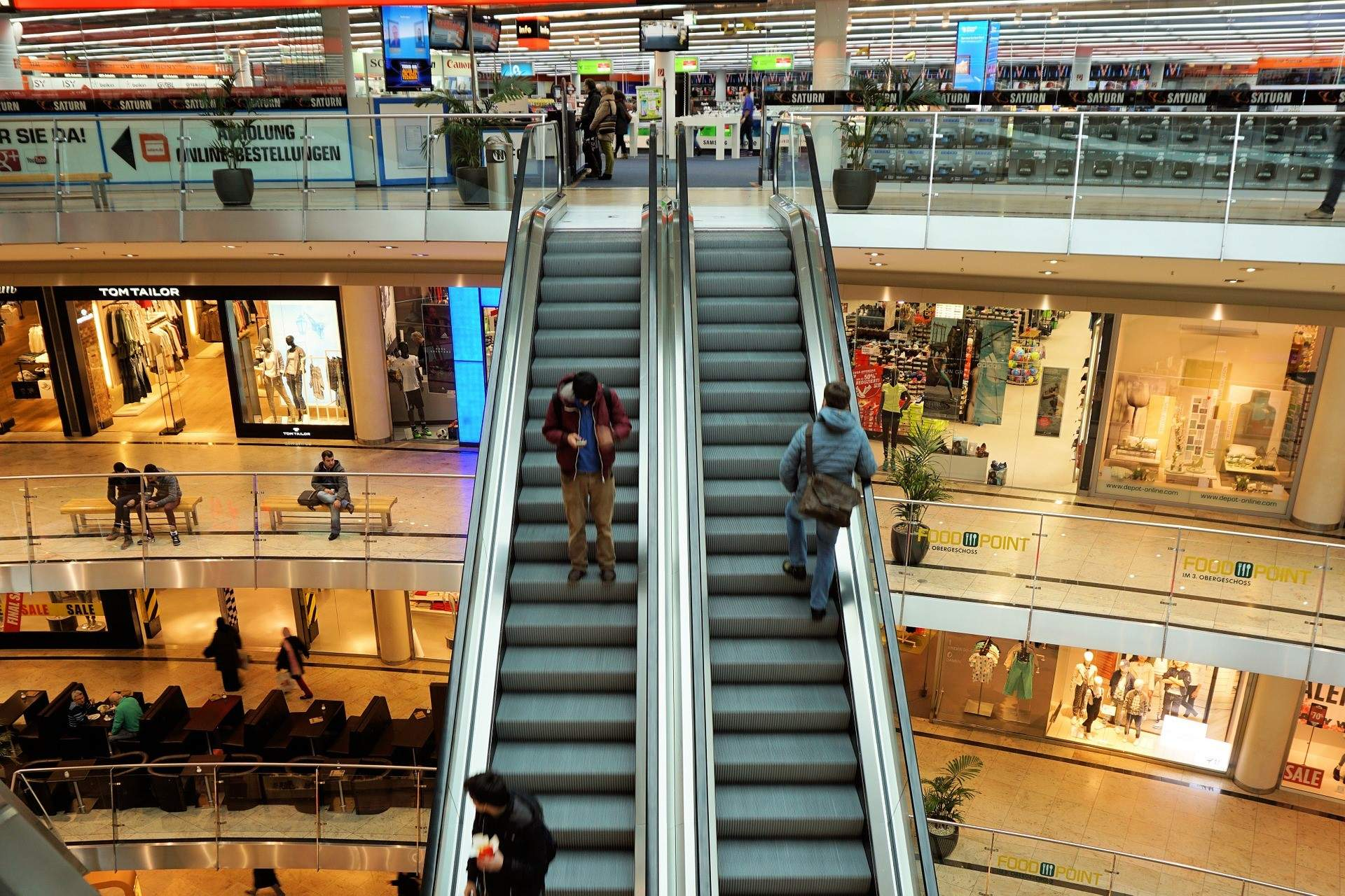 Shopping center patrons on escalator